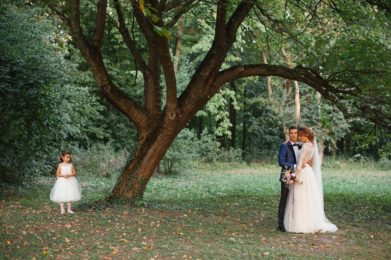 Fotografie de nunta cu miri la apus sub un copac