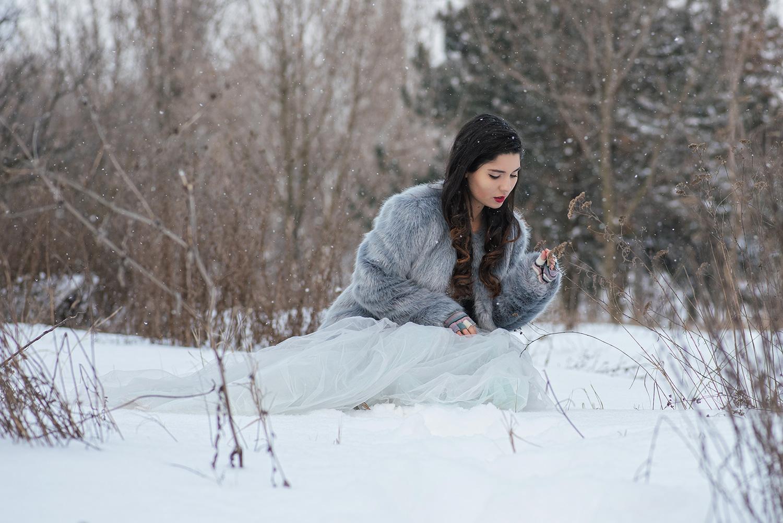 Mireasa in rochir de mireasa in zapda admira o floare, trash the dress iarna