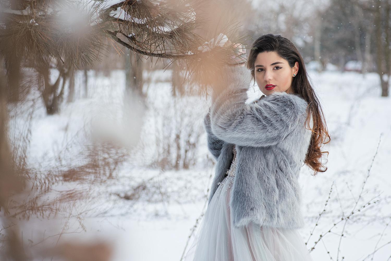 Mireasa care pozeaza in apropierea unui brad cu zapada la sedinta foto profesionista iarna