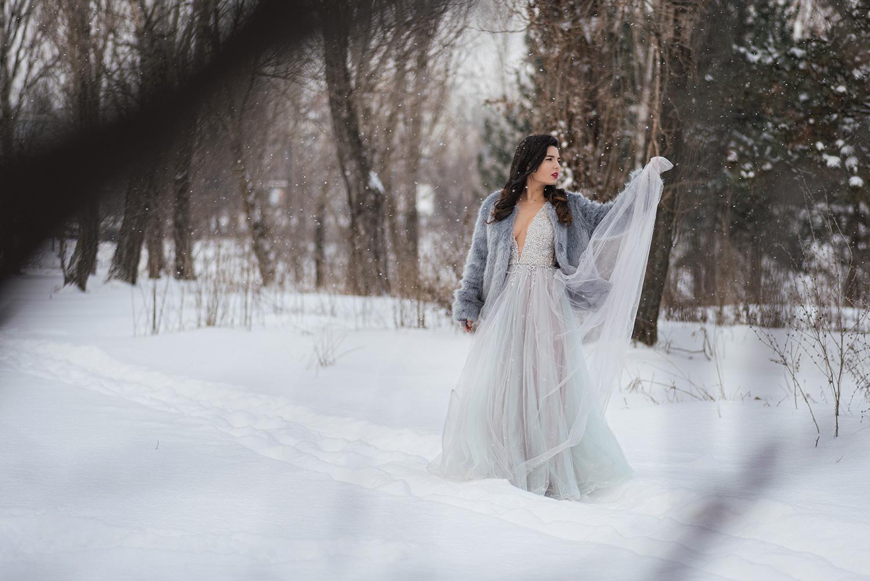 Mireasa la sedinta foto in zapada ridica un voal din fusta rochiei si il admira, trash the dress iarna