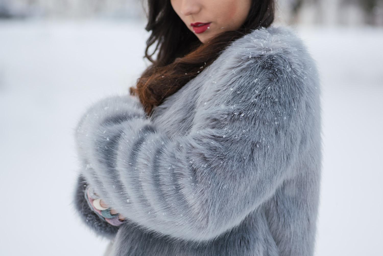 Maneca haina de blana cu fulgi mici de zapada in ea si pe fundal gura miresei cu ruj rosu, trash the dress iarna