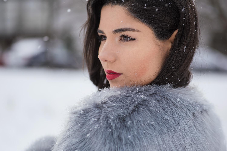 Tanara mireasa cu parul brunet care pozeaza din profil iarna la sedinta foto profesionista, in timp ce ninge