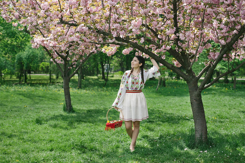 fotograf profesionist, fata frumoasa in costum popular traditional romanesc, costum popular, costum traditional. livada inflorita, pomi infloriti, oua de Paste, cos cu oua de Paste