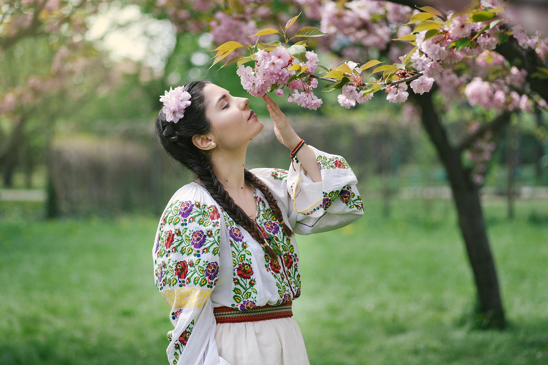 fotograf profesionist, fotograf, fotograf robert dumitru, fata frumoasa in costum popular traditional romanesc, tanara femeie miroase o floare, ramura de cires inflorita, cires inflorit, sedinta foto de portret, sedinta foto de Paste