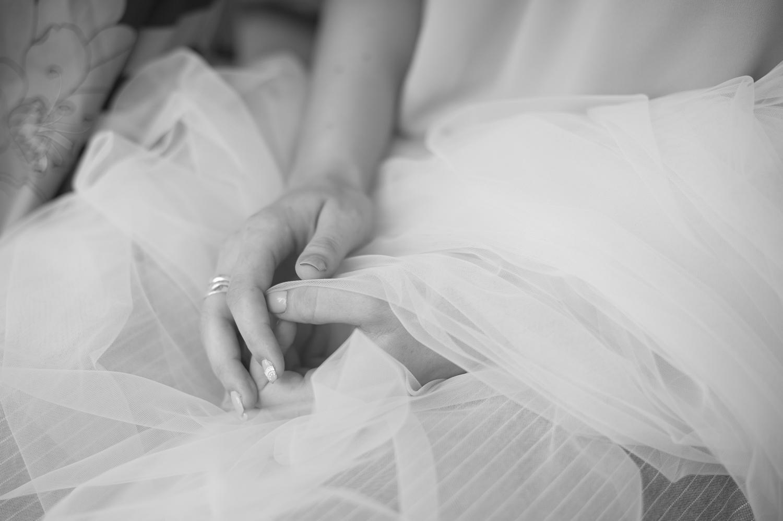 Fotografie alb-negru cu mainile si voalul miresei