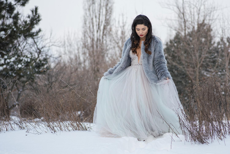 Mireasa tanara cu parul brunte tine de rochie la sedinta de trash the dress, trash the dress iarna