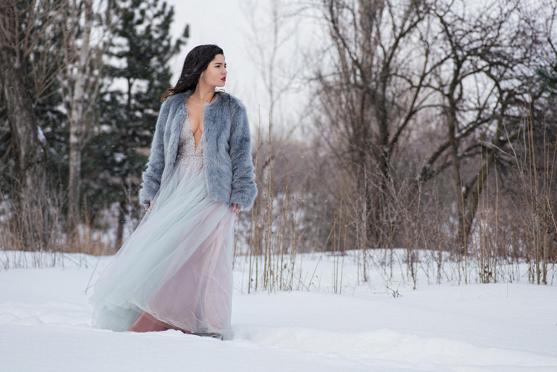 Mireasa cu rochie de mireasa decoltata si hain ade blana scruteaza zarile, trash the dress iarna