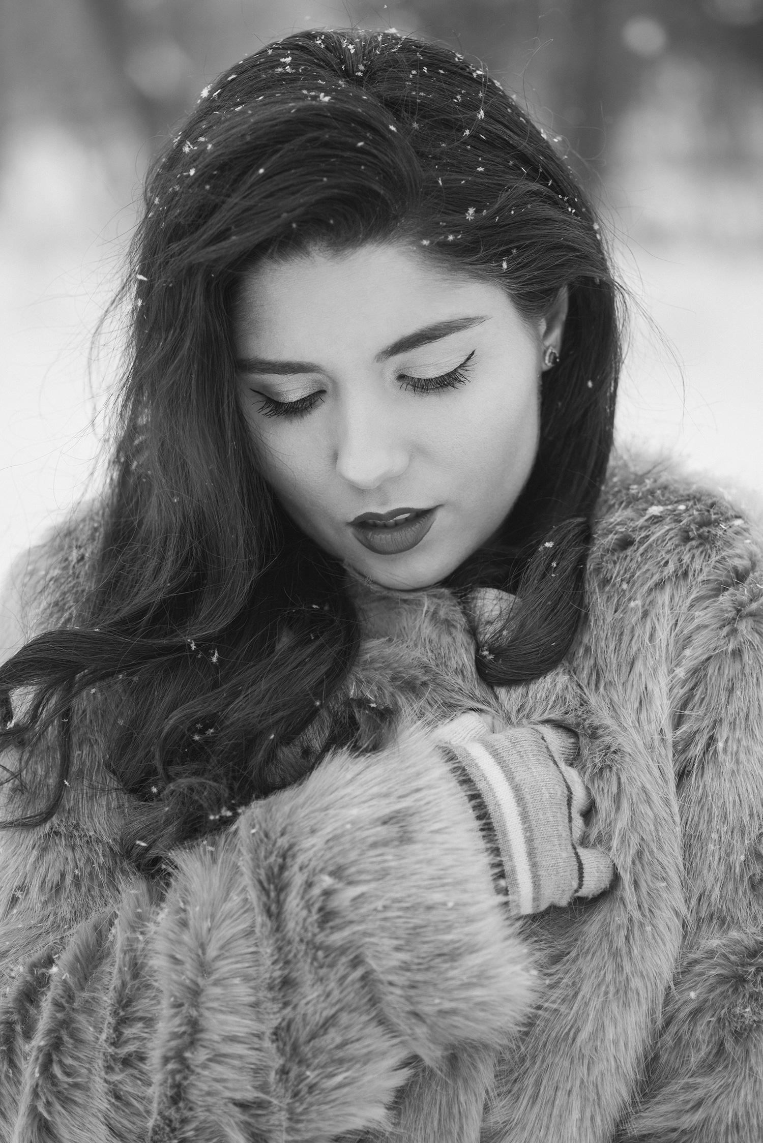 Fotografie alb-negru de portet cu mireasa in prim-plan care priveste inspre in jos in timp ce ninge